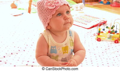 Baby in a pink knitted hat, looks up and smiles. 4k video