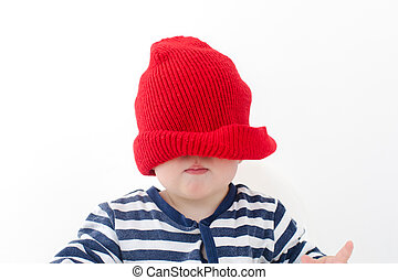 Baby in a red hat pulled over his face studio