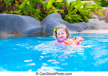 Baby in a swimming pool - Adorable little baby girl having...