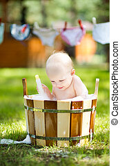 baby in a wooden basin with foam