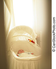 Baby in Bassinet - Baby in bassinet with curtains fluttering...