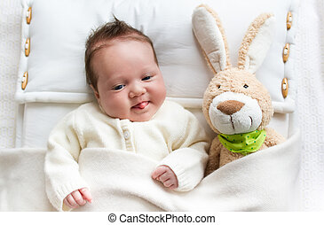 Baby in bed with bunny toy