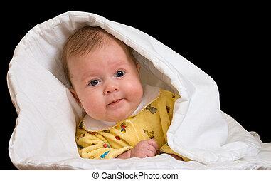 Baby in blanket over black