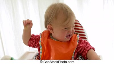 Baby in child seat crying while eating - Upset baby in...