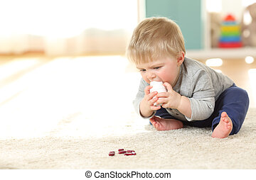 Baby in danger playing with a bottle of medicines