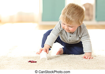 Baby in danger playing with a bottle of pills