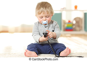 Baby in danger playing with an electric plug