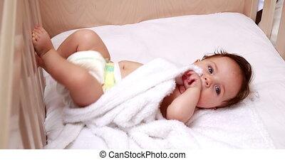 Baby in diaper lying in crib at home in bedroom
