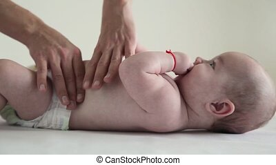 baby in diapers lying on his back receiving a massage tummy