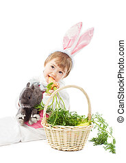 baby in easter bunny costume eating fresh carrot, kid girl holding hare rabbit over white background