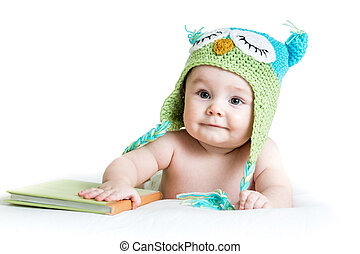 baby in funny knitted hat owl with book on white background...