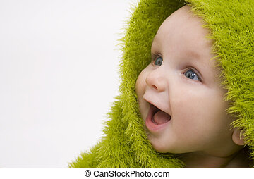 Baby In Green - A beautiful smiling baby wrapped in a furry...