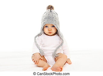 Baby in grey knitted hat on a white background