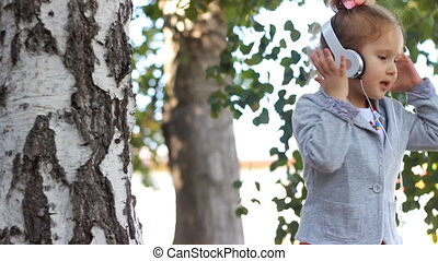 Baby in headphones listening to music and singing a song in a park with birches