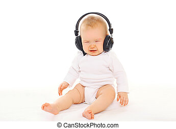Baby in headphones sitting on a white background