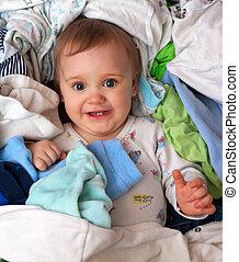 Baby in heap of wear - Happy baby girl in heap of baby's...