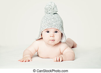 Baby in knitted hat lying on white blankett, portrait. Pretty little child (3 months old)
