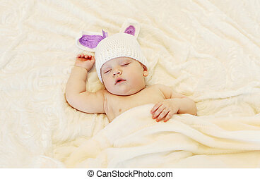Baby in knitted hat with a rabbit ears sleep lying on bed under blanket