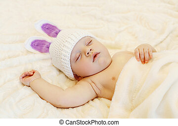 Baby in knitted hat with a rabbit ears sleep lying on bed