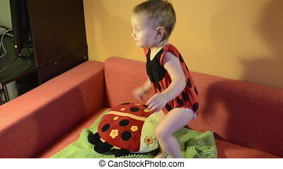 Baby in ladybird costume plays with toy on the couch