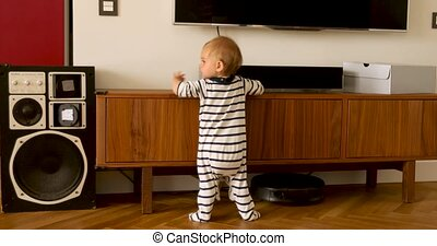 Baby in overalls standing in living-room - Back view of...