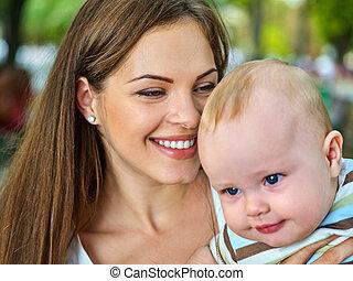 Baby in park outdoor. Kid on mom's hands.