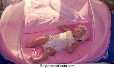 Baby in pink bassinet at the beach