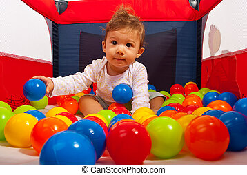 Baby in playpen with balls