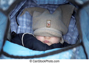 Baby in Pram - Baby in a pram with hat over his eyes....