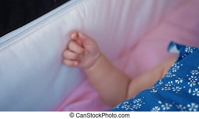 Baby in pram moving her hand - Slow motion close-up shot of...