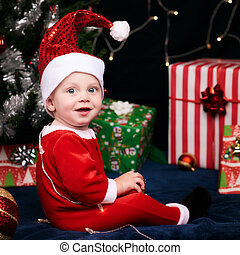 Baby in santa outfit looking over shoulder at camera -...