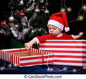 Baby in santa outfit sitting inside a wrapped gift box - 9...