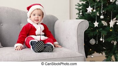 Baby in santa suit sit on sofa with Christmas tree - Baby 1...