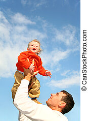 baby in sky on father's hands