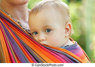 Baby in sling looking outdoor. Mother is carrying her child.