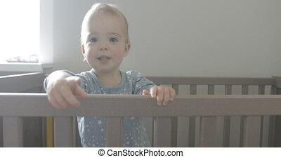 Baby in the crib looks around and smiles - Kid in the crib...