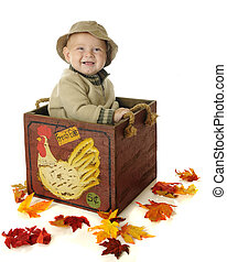 A happy baby boy sitting in a wooden egg crate surrounded by colorful leaves. On a white background.