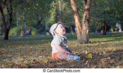 Baby in the forest. Falling autumn leaves. Slow Motion 100 fps.