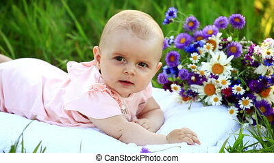 Baby in the grass with flowers.