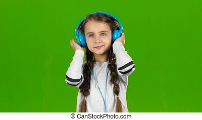 Baby in the headphones is listening to music. Green screen -...