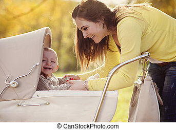 Baby in vintage pram with his mother - Happy child in...