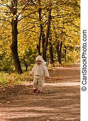 Baby in white in autumn
