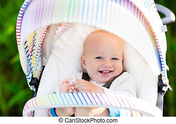 Baby in white stroller - Baby boy in white sweater sitting...