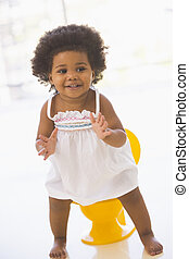 Baby indoors going on potty smiling