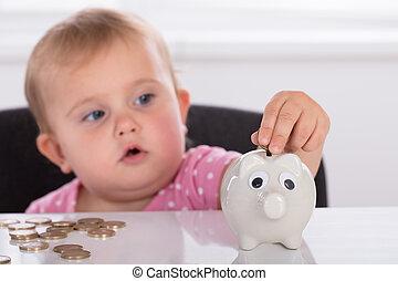 Baby Inserting Coin In Piggybank