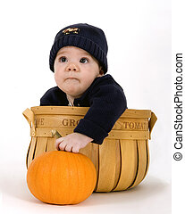 Baby inside a fruit basket with the words Home Grown on it, holding on to a pumpkin