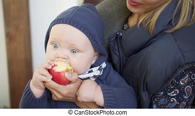 Baby is eating an apple on mother hands