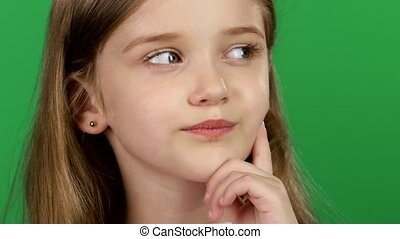 Baby is looking at the side, she is thoughtful. Green screen. Close up