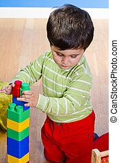 Baby is playing with educational toys over wooden background