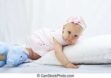 baby is playing with pillow over white background